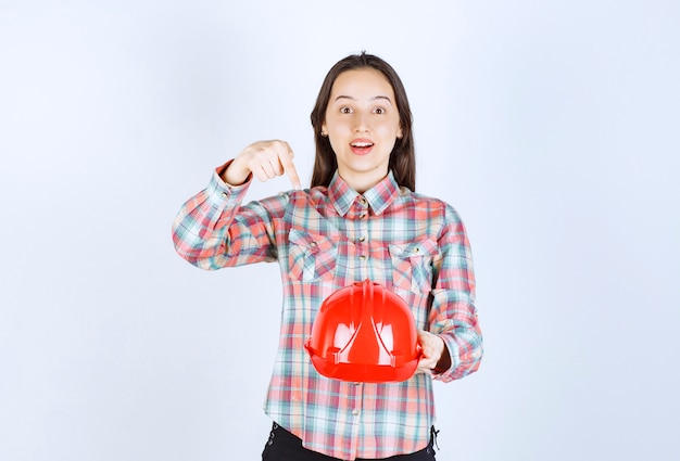 Молодая красивая женщина архитектора, держащая шлем безопасности над белой стеной.