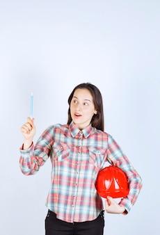 Молодая красивая женщина архитектора, держащая шлем безопасности с ручкой.