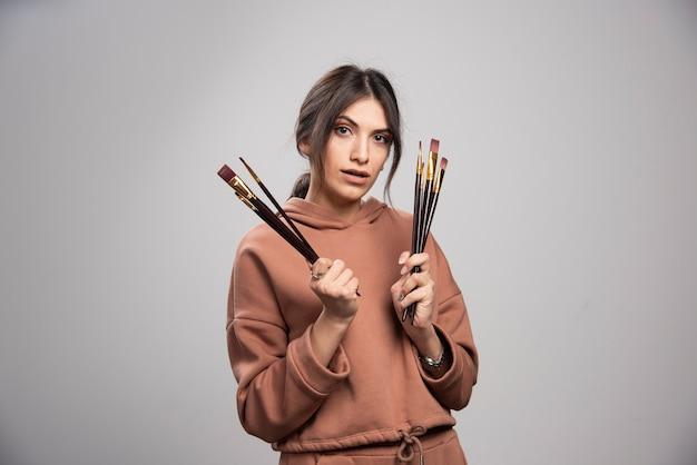 Giovane bella artista che tiene diversi pennelli