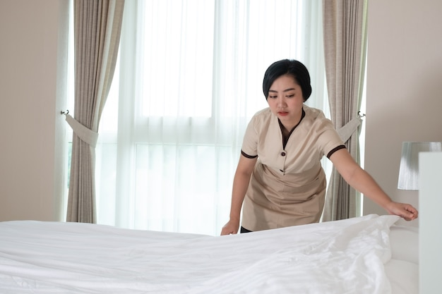 Young beautiful asia maid arranging blanket on the bed in hotel room