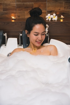 Young beautiful asia woman takes bubble bath