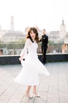 Молодая красивая азиатская невеста в белом свадебном платье танцует на террасе древнего города.