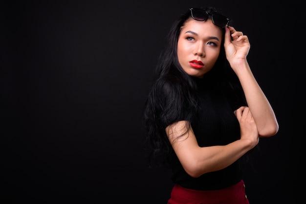 검은 벽에 젊은 아름 다운 아시아 사업가