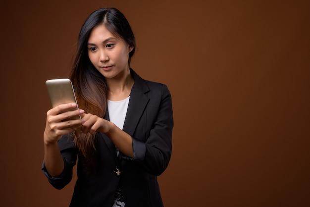 Молодая красивая азиатская бизнес-леди на коричневом фоне