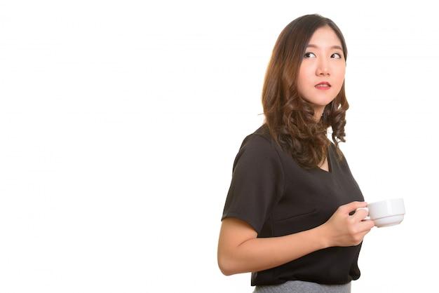 Молодая красивая азиатская деловая женщина держит чашку кофе во время мышления