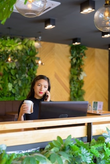 コーヒーショップで電話で話しながらコーヒーを保持している若い美しいアジア女性実業家