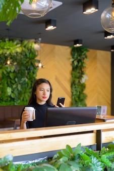 コーヒーショップで電話を使用しながらコーヒーを保持している若い美しいアジア女性実業家