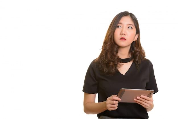 Молодая красивая азиатская деловая женщина держит цифровой планшет во время мышления