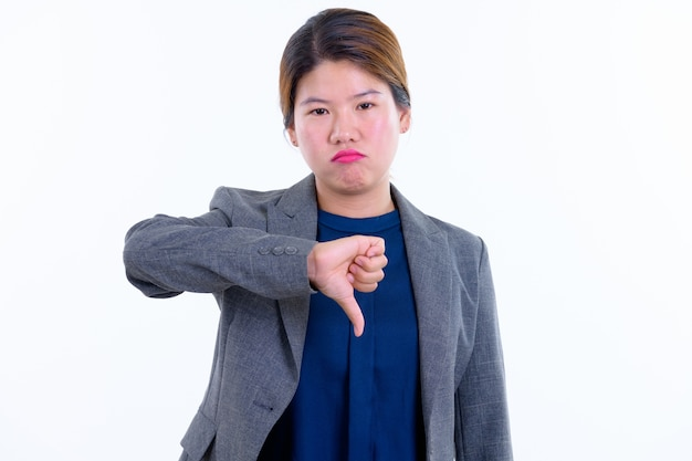 Young beautiful asian businesswoman isolated against white wall