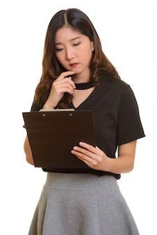 Молодая красивая азиатская бизнес-леди читает буфер обмена, думая