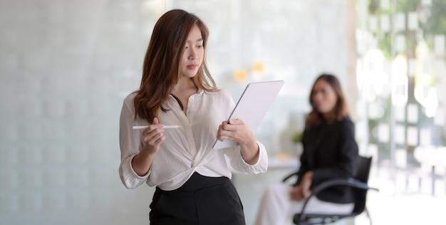 Молодая красивая азиатская коммерсантка читая некоторый документ стоя в offic