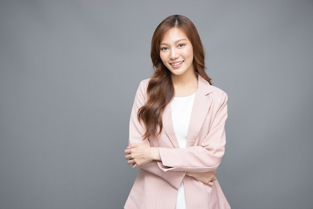 회색 배경에 격리된 분홍색 양복을 입고 서서 웃고 있는 젊고 아름다운 아시아 여성
