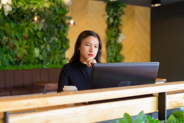 コーヒーショップでノートパソコンを使用しながら考えて若い美しいアジア女性実業家