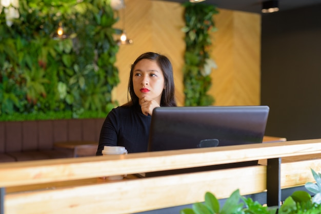 コーヒーショップでノートパソコンを考えて若い美しいアジア女性実業家