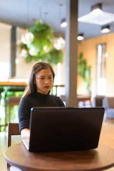 Молодая красивая азиатская деловая женщина с помощью ноутбука и сидя в кафе