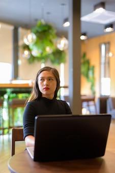 ラップトップを使用して、コーヒーショップで考えて若い美しいアジア女性実業家