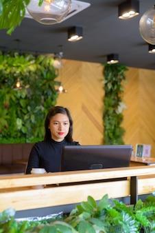 コーヒーショップでラップトップを使用して若い美しいアジア女性実業家
