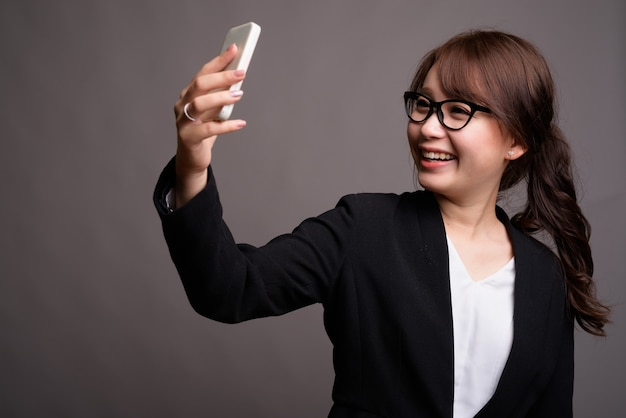 Young beautiful asian businesswoman using mobile phone