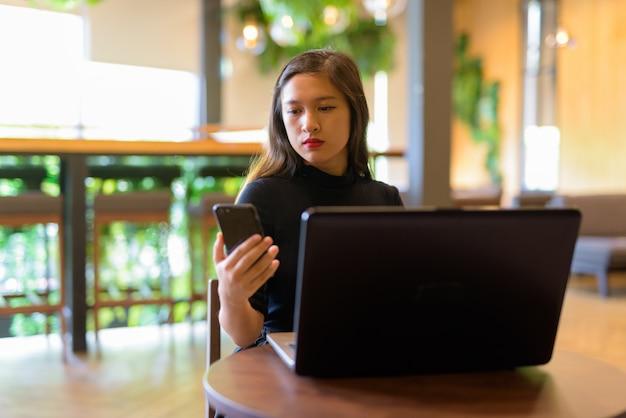 コーヒーショップで電話とラップトップを使用して若い美しいアジア女性実業家