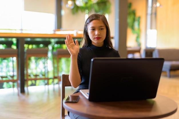 Молодая красивая азиатская бизнес-леди видеосвязь с ноутбуком в кафе