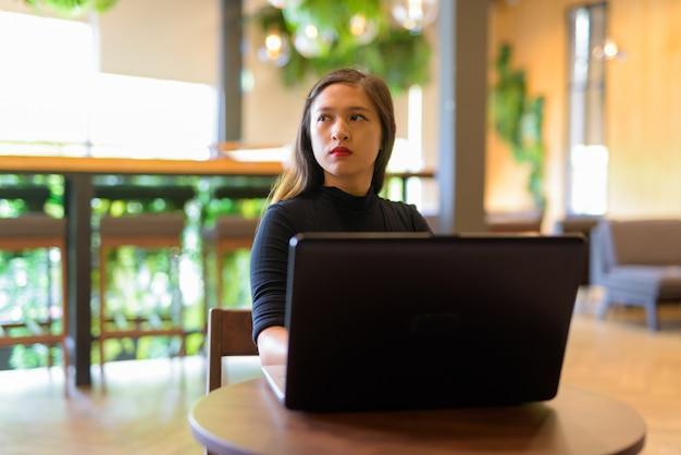 ノートパソコンを考えて、コーヒーショップに座っている若い美しいアジア女性実業家