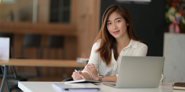 Young beautiful asian businesswoman working on her project with laptop computer and smiling to the camera