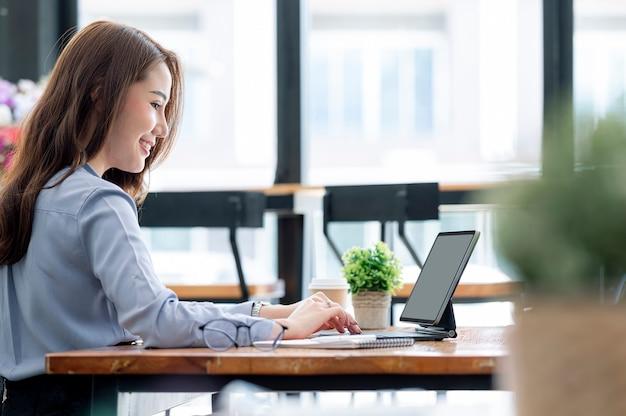 Молодая красивая азиатская коммерсантка работая на таблетке с счастьем, сидя за столом в современном офисном помещении.