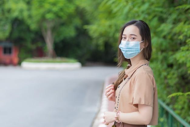 若い美しいアジアの大学生はコロナウイルスを防ぐためにマスクを着用します
