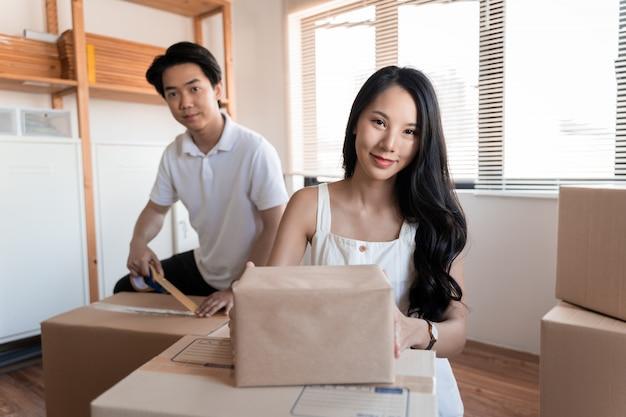 Молодая красивая азиатская влюбленная пара переезжает в новый дом, сидя на полу очень радостный и веселый для новой квартиры вокруг картонных коробок
