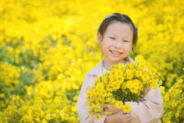 黄色の菊畑で花と笑顔を保持している若い美しいアジアの女の子の子供。
