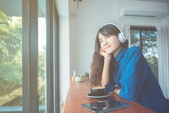 Young beautiful asian girl drinking coffee while listening music