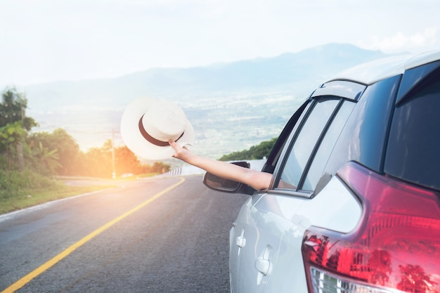 Young beautiful asian girl holding hat weave and reach out of the car at sunset