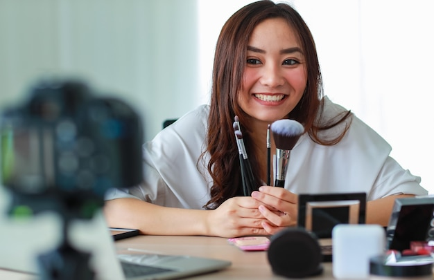 Young and beautiful asian girl shows various face brushes to camera with smile and happy during broadcast video recording about cosmetics content and review. online selling and marketing concept.