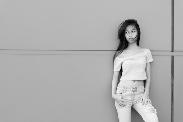 Young beautiful asian girl thinking and looking at distance while leaning on concrete wall outdoors