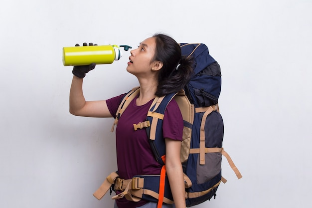 Young beautiful asian hiker woman drinking water on white background