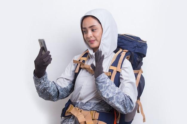 Молодая красивая азиатская туристическая женщина с помощью мобильного телефона на белом фоне