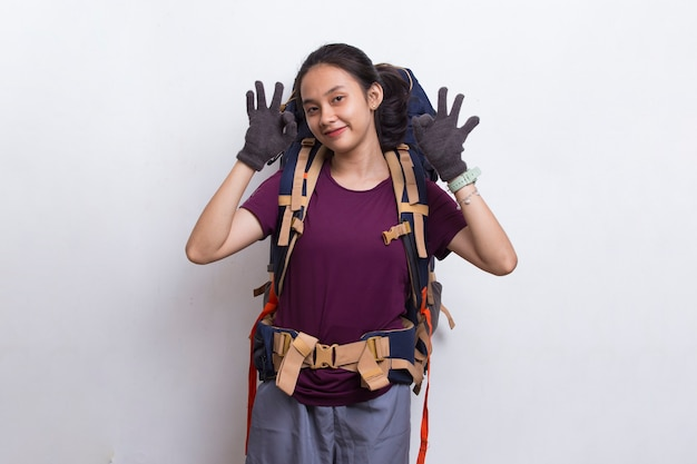 白い背景の上の親指をokジェスチャーを示すバックパックを持つ若い美しいアジアのハイカーの女性