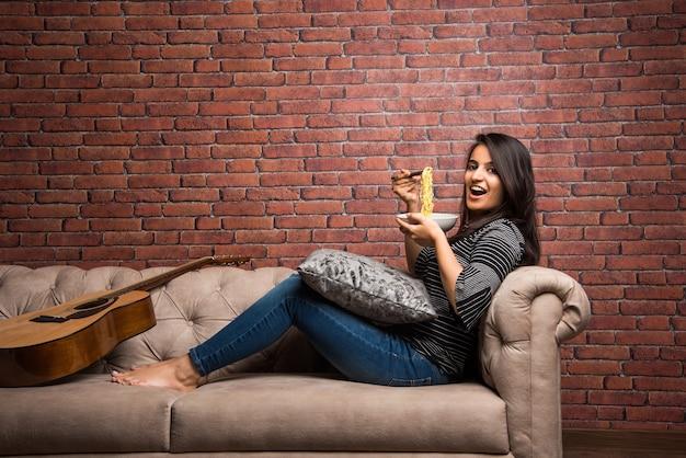 Молодая красивая азиатская индийская девушка ест лапшу быстрого приготовления, используя палочки для еды. стоя, изолированные на белом фоне. выборочный фокус