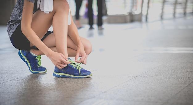 Young beautiful asian model woman jogger running in morning sit