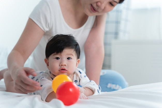 Young beautiful asian mother with her little cute baby on bed.