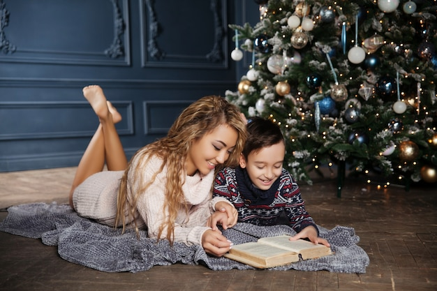Young beautiful asian mother with her little son sitting near a decorated christmas tree and reading a book.
