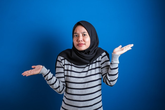若い美しいアジアのイスラム教徒の学生は彼女の腕をすくめる、私が知らないジェスチャーをする、青い背景に対して何も助けることができない