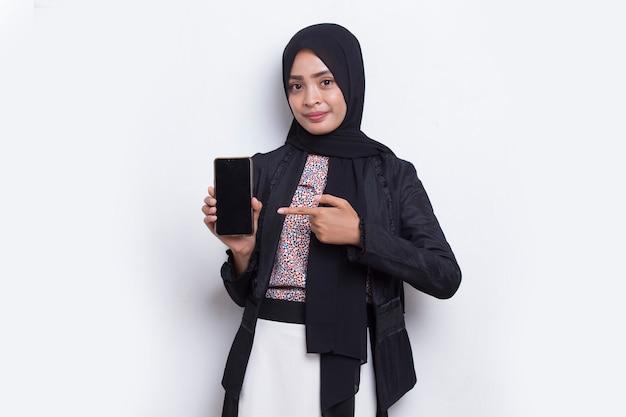 Молодая красивая азиатская мусульманская женщина демонстрирует мобильный телефон на белом фоне