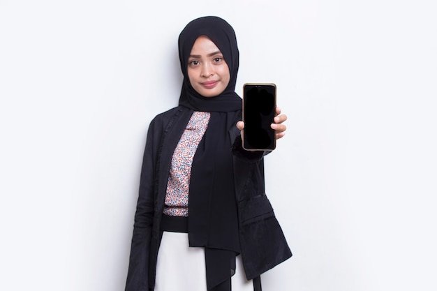 Young beautiful asian muslim woman demonstrating mobile cell phone isolated on white background