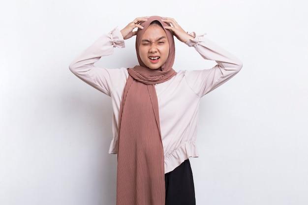 Молодая красивая азиатская мусульманская женщина почесывает голову рукой, изолированной на белом фоне