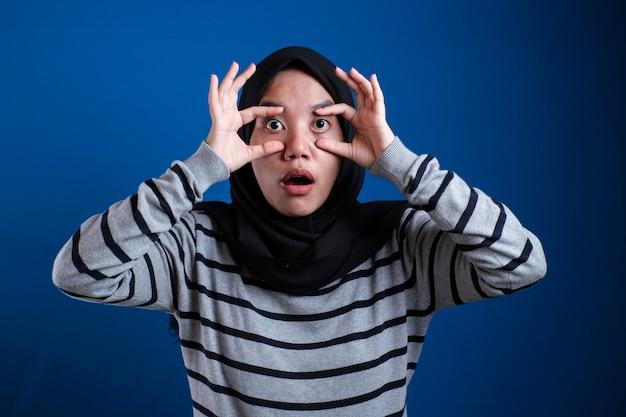 孤立した青い背景の上にアラブのヒジャーブを身に着けている若い美しいアジアのイスラム教徒の女性指で目を開けようとすると、眠くて朝の疲れに疲れています