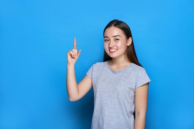 若い美しいアジア人の笑顔と青い壁に親指を表示