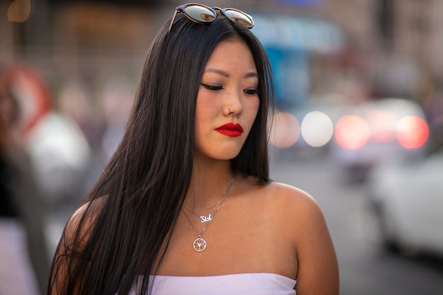 Young beautiful asian smiling happy woman walking on city streets on sunny summer day
