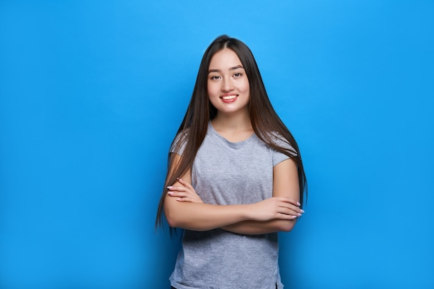 Young beautiful asian smiling with crossed arms on blue wall