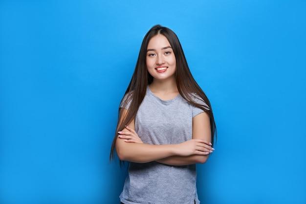 Молодая красивая азиатка улыбается со скрещенными руками на синей стене